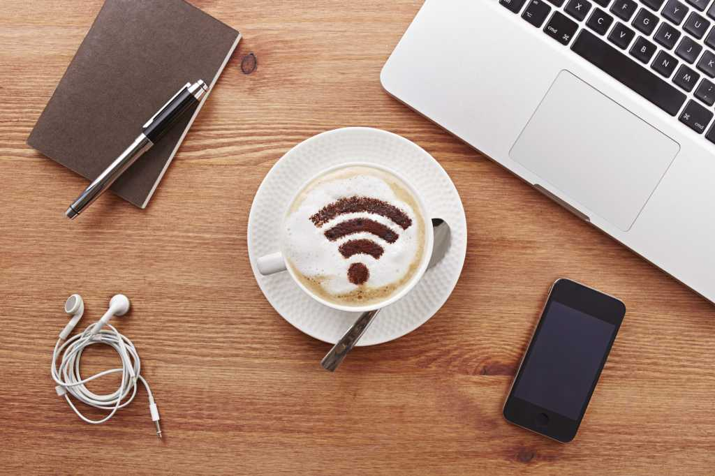 Still life of mobile devices on desk with coffee with wifi symbol